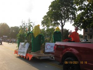 Truck pulling trailer with corn stalk float.