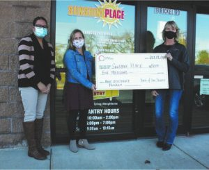 Three people holding large check of $5000 in front of building.