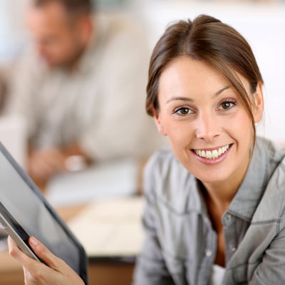 Smiling female holding tablet device
